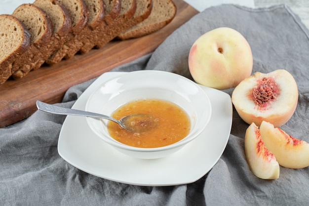 A white plate with peach jam and slices of brown bread.