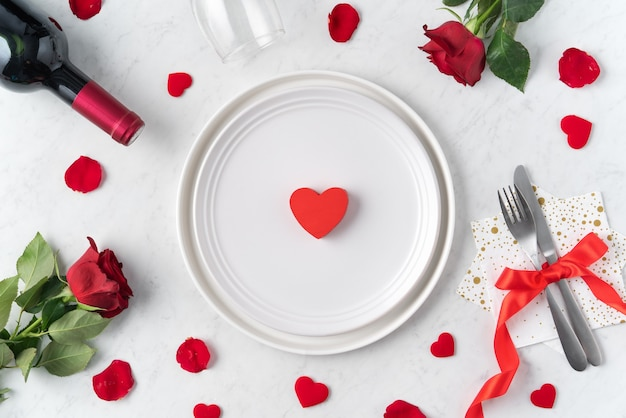 White plate with red rose flower on marble white table background for valentine's day dating holiday meal concept.