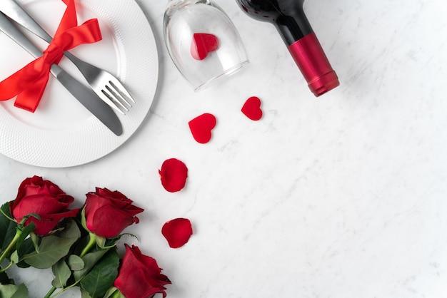 발렌타인 데이 데이트 휴가 식사 개념에 대 한 대리석 흰색 테이블 배경에 빨간 장미 꽃과 흰색 접시.