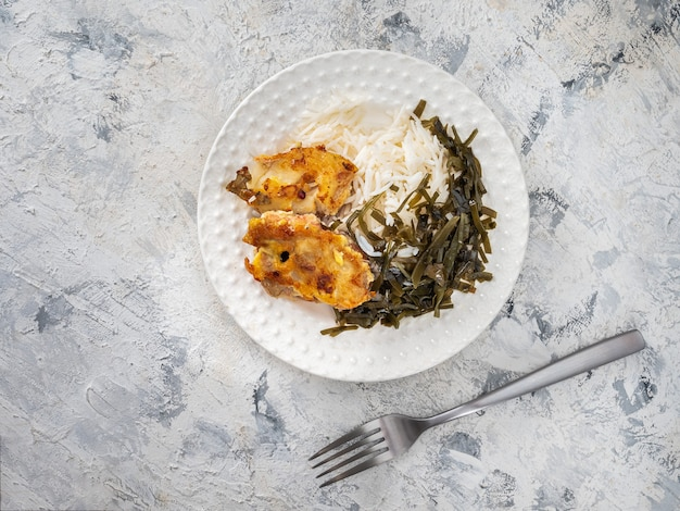 White plate with rice and sea fish, seaweed salad