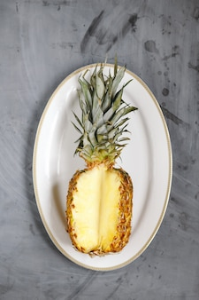 White plate with ripe sliced pineapple on grey concrete background.