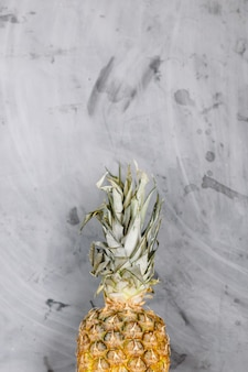 White plate with ripe whole pineapple on grey concrete background. copyspace.