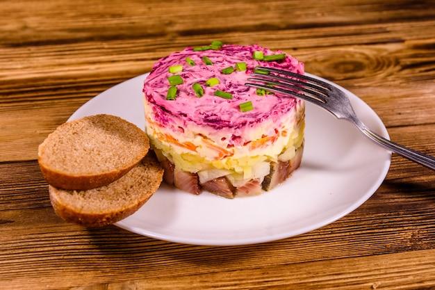 Белая тарелка с традиционным русским новогодним салатом из сельди под шубой и ржаным хлебом на деревенском деревянном столе