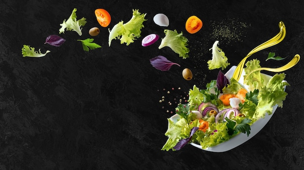 A white plate with salad and floating in the air ingredients: olives, lettuce, onion, tomato, mozzarella cheese, parsley, basil and olive oil. copy space.