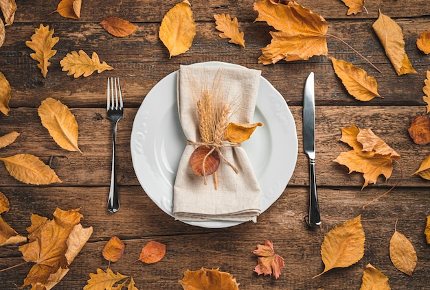 A white plate with a serving napkin and cutlery on a wooden background with autumn leaves