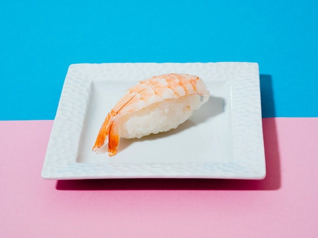 White plate with shrimp sushi on a blue and rose background