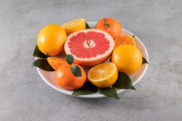 대리석 표면에 슬라이스 오렌지, 레몬, 자몽과 화이트 플레이트
