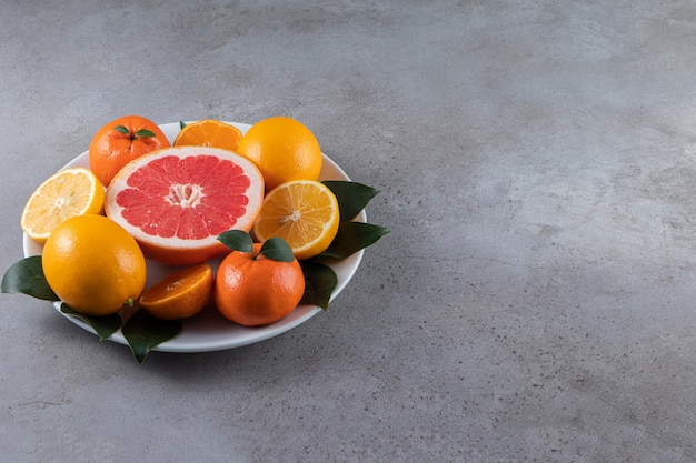White plate with sliced orange, oranges and grapefruit on marble table.