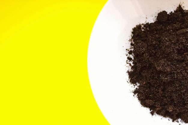 노란색 배경에 흙이 있는 흰색 접시, 성장 단계 개념. 평면도. 가정 정원 가꾸기. 새로운 삶.