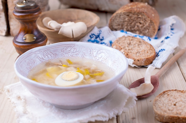 White plate with soup with mushrooms and egg. wooden background, bread and spices