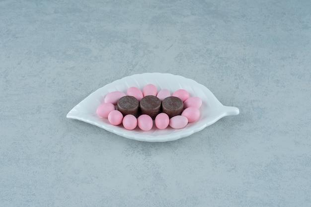 Un piatto bianco con dolci caramelle rosa e biscotti al cioccolato su superficie bianca
