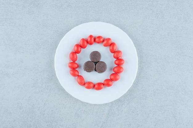Un piatto bianco con dolci caramelle rosse e biscotti al cioccolato su sfondo bianco. foto di alta qualità