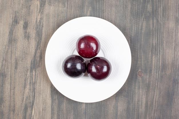 Un piatto bianco con tre prugne fresche su un tavolo di legno. foto di alta qualità