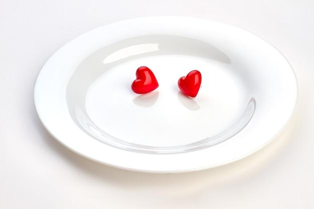 두 개의 빨간색 하트와 화이트 플레이트입니다. 흰색 도자기 접시, 복사 공간에 두 개의 작은 마음. 발렌타인 데이 개념.