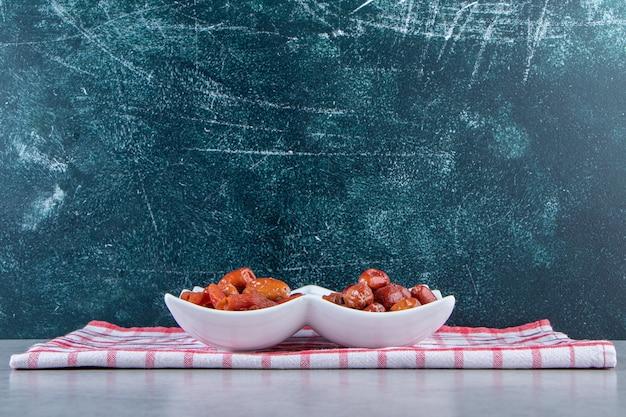 돌 배경에 다양 한 맛 있는 말린 과일과 흰색 접시.