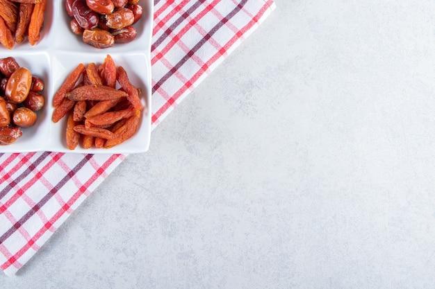 Белая тарелка с различными вкусными сухофруктами на камне.