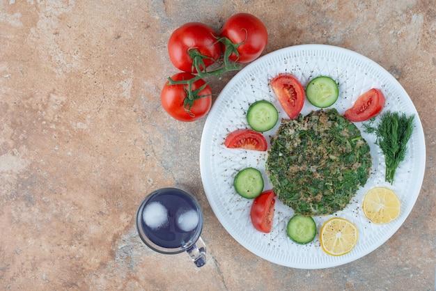 Un piatto bianco con verdure e una tazza di succo