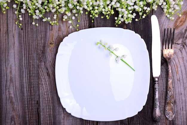 White plate with vintage iron cutlery on a gray wooden surface