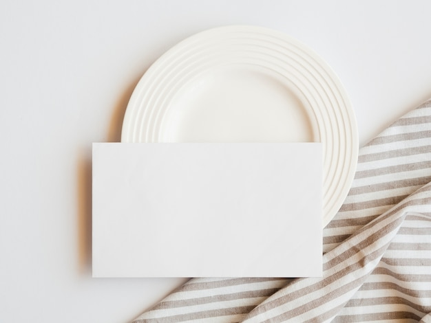 White plate with a white blank and a striped brown and white tablecloth on a white background