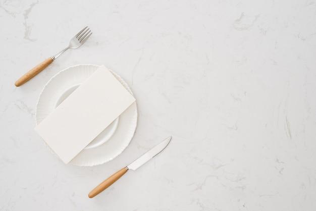 フォークとナイフで食べ物のない白いプレート