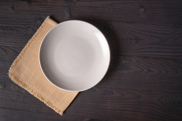 White plate on a yellow napkin on a wooden table, top view, place for a menu or recipe.