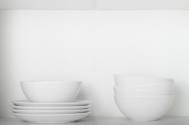 찬장에 선반에 하얀 접시와 그릇.