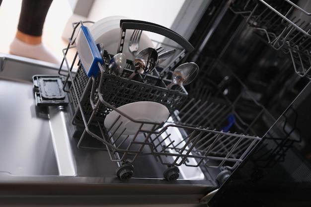 Белые тарелки и столовые приборы в открытой посудомоечной машине крупным планом