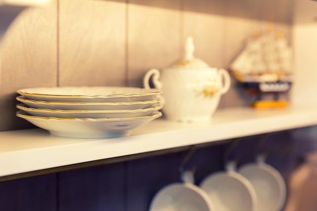 Белые тарелки и посуда в шкафу