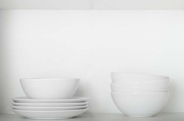 White plates and bowls on a shelf in the cupboard.