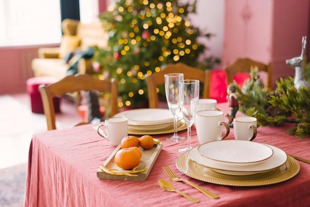 クリスマスのお祝いディナーのサービングの白いプレート、シャンパングラス、みかん