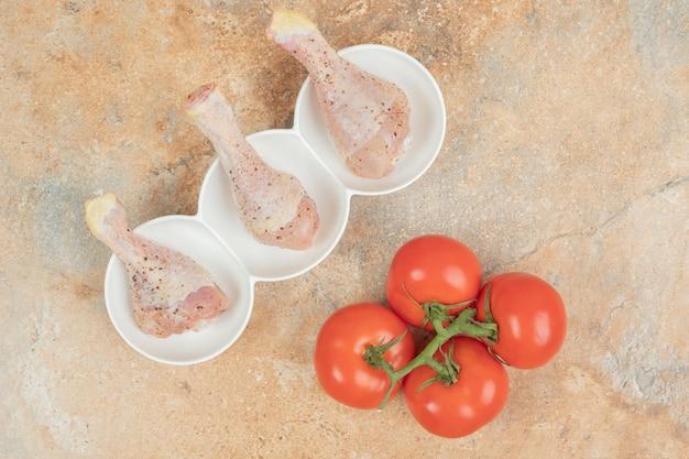A piatti bianchi di cosce di pollo con spezie