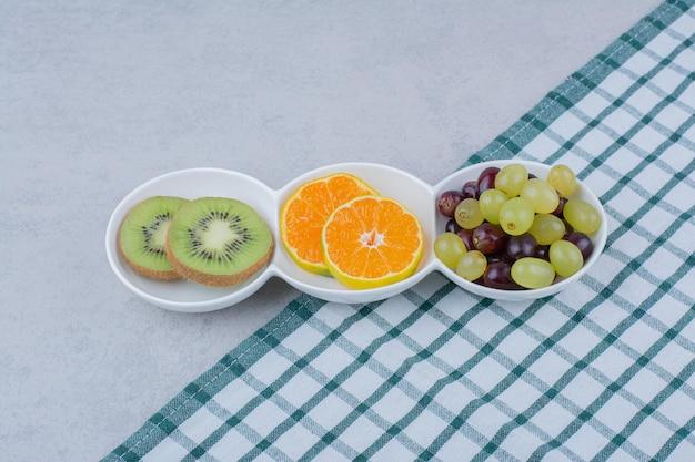 Piatti bianchi di frutta fresca sulla tovaglia. foto di alta qualità