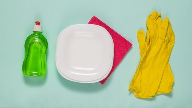 Белые тарелки, зеленое моющее средство и желтые резиновые перчатки