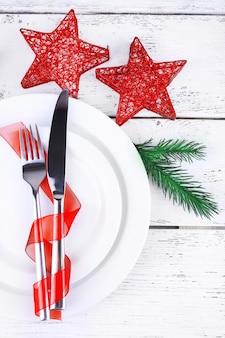 木製のテーブルに白い皿、ナイフ、フォーク、ナプキン、クリスマスの飾り