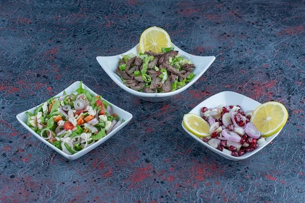 Piatti bianchi di carne e insalate di verdure