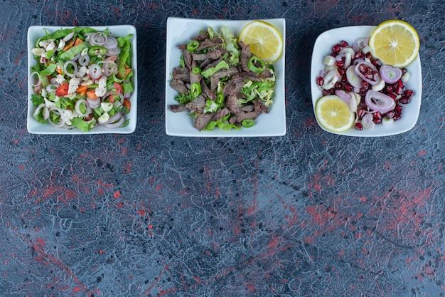 Белые тарелки мясных и овощных салатов