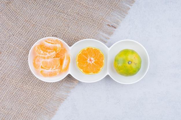 Piatti bianchi di mandarini sbucciati su tela di sacco