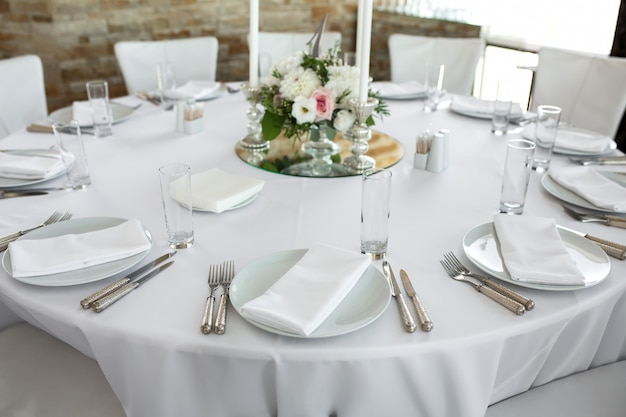White plates, silverware, white tablecloth and white room. banquet table for guests