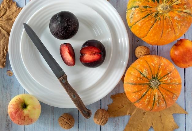 Белые тарелки со свежими спелыми сливами, тыквами, грецкими орехами, яблоком и нектарином на синем фоне.