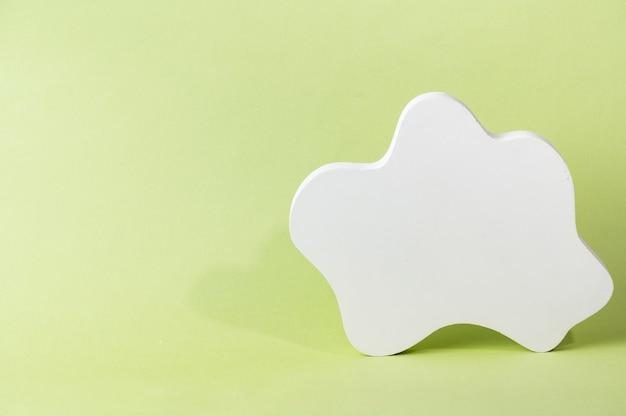 緑の背景に白い表彰台。テンプレート、プレゼンテーション製品のモックアップ。パステルカラーは、幾何学的な形で構成をスタイリングしました。最小限のコンセプト。製品表彰台。