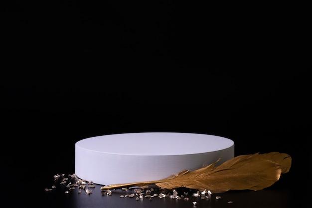 황금 깃털과 작은 수정이 있는 검은 배경에 흰색 연단. 제품 연단, 화장품 프레젠테이션. 창의적인 모의. 미용 제품을 위한 받침대 또는 플랫폼. 미니멀한 디자인.