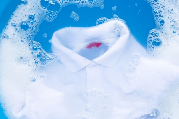 White polo shirt soak in powder detergent water dissolution, washing  cloth.