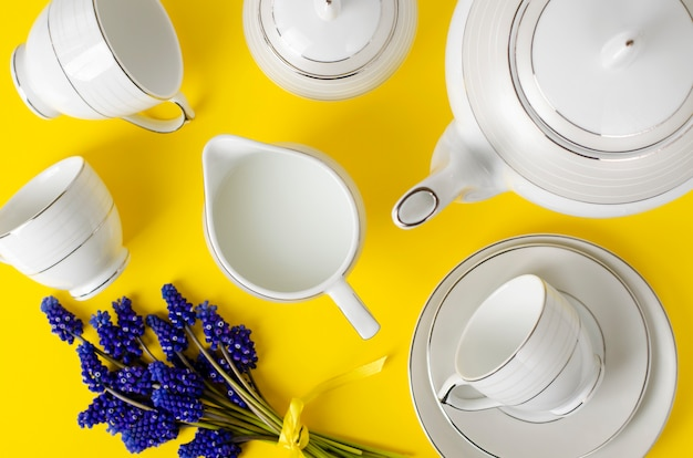 White porcelain coffe or tea set with muscari flowers on yellow