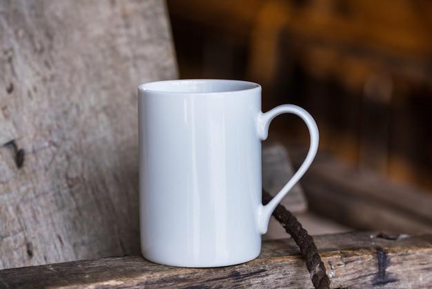 白い磁器のコーヒーカップ、古い木製のテーブルのマグカップ