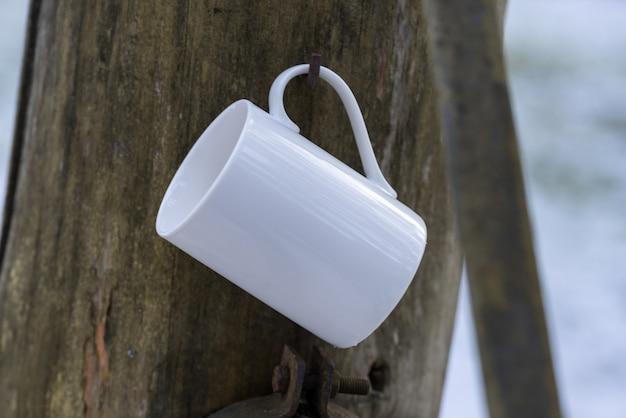 白磁のコーヒーカップ、屋外の凍った雪のマグカップ