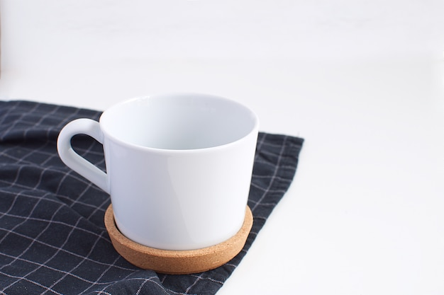 White porcelain cup and checkered black napkin