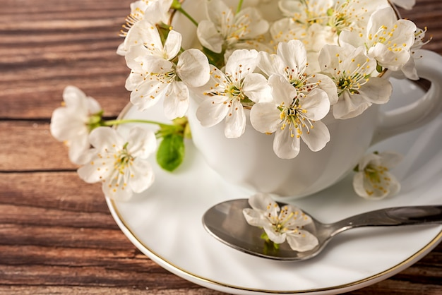 White porcelain cup in it flowers are white from the apple tree. on a brown background. spoon on a platter.