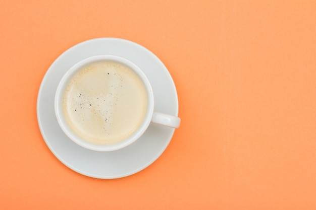 コピースペースと桃色の背景に受け皿にブラックコーヒーの白い磁器カップ。上面図 Premium写真