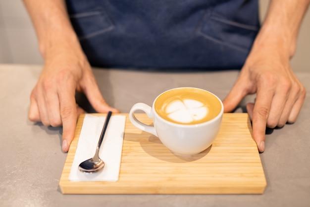 Белая фарфоровая чашка капучино и маленькая ложка с бумажной салфеткой на деревянном подносе, которую держит молодой официант или бариста