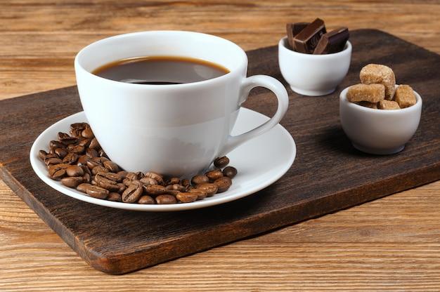 Белая фарфоровая чашка кофе, кофейные зерна, миски с тростниковым коричневым